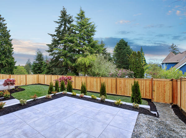 Concrete patio next to grass and loose stone.