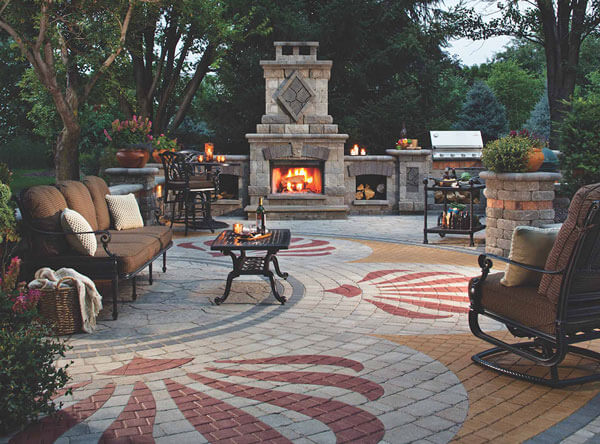 Outdoor patio with fireplace, bbq, and colored paver patterns.