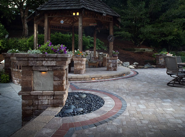 Backyard landscape with loose rocks, patio table, and rustic gazebo.