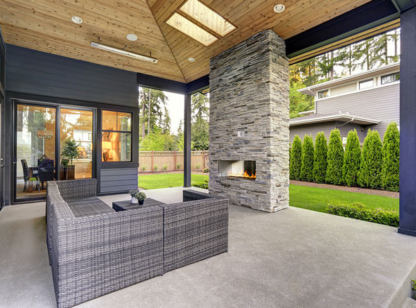 Covered patio with modern fireplace and vaulted ceiling.