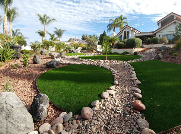 Tiki inspired backyard with artificial grass and loose stones.