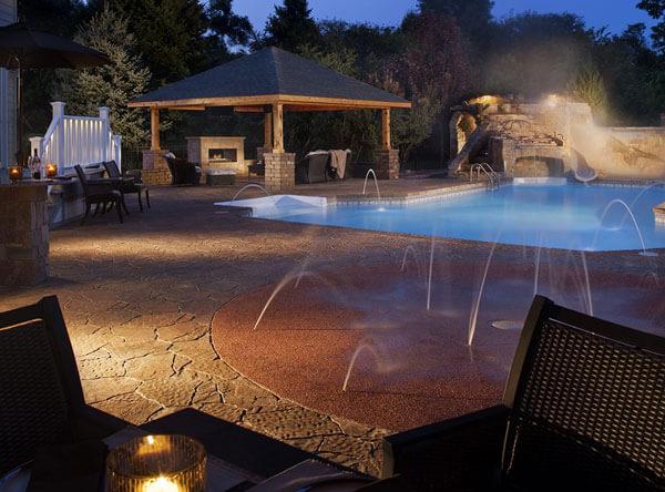 Backyard landscape with gazebo, pool, and splash pad.