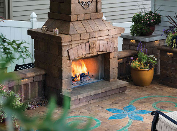 Outdoor fireplace with blue paving stones laid in a flower pattern.