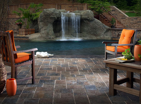 Backyard pool area with a waterfall and paving stones.