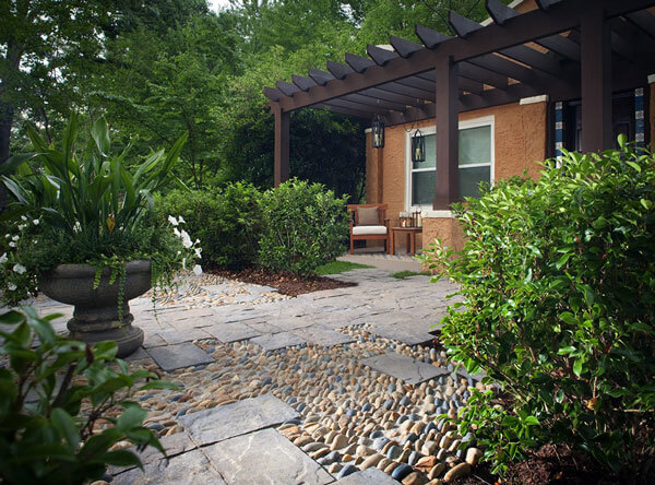 Patio with loose stones set with concrete and pavers, with a dark brown pergola.
