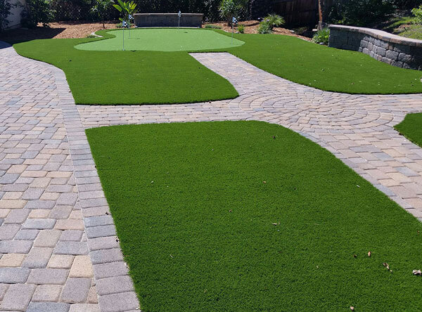 Putting green with artificial grass areas next to a pool.