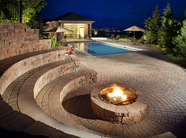 Triple row seating area surrounding a fire pit with a pool close by.