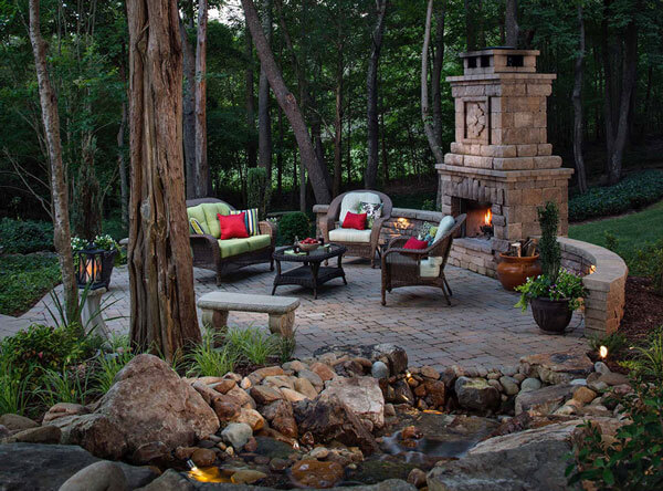 Woods patio area with seating and an outdoor fireplace.