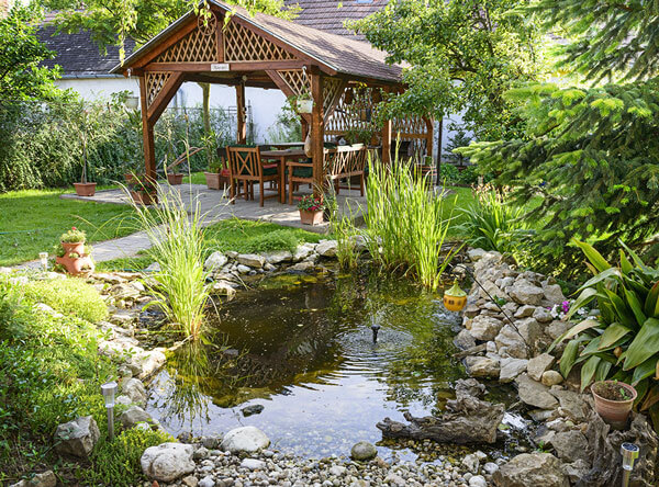 A small pond next to a beautiful garden with bench.