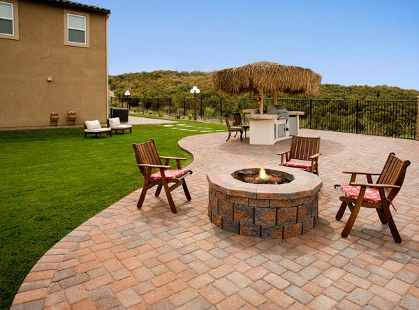 Tiki inspired patio with outdoor firepit and outdoor kitchen.