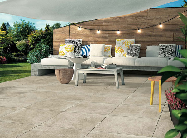 Modern patio with clean concrete, wood siding, and sail shade.