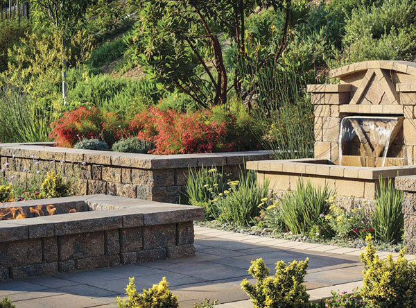 Landscape with alot of vegetation, accompanied with a fire pit and small waterfall.