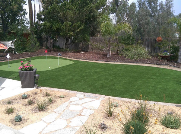 Putting green made of artificial grass with a hammock and drought resistant plants.