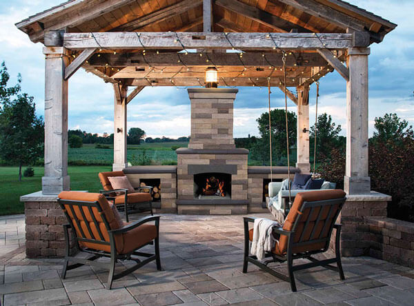 A gazebo covering an outdoor patio area with bench swing and outdoor fireplace.