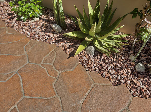 Beautiful red flagstone pavers next to color matching loose rock stones and drought tolerant plants.