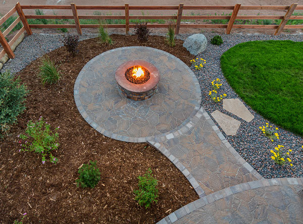 Outdoor firepit surrounded with pavers and tree bark.