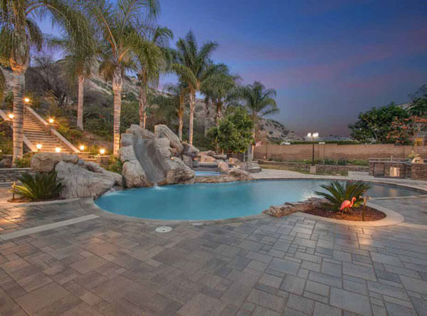 Pool area with slide and beautiful paving stones.