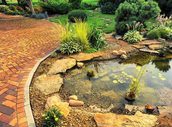 Pond next to red pavers and loose stones.