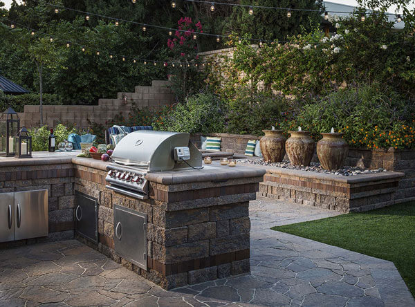 Paving stones laid down next to an outdoor kitchen and jar fountains on a raised wall bed.