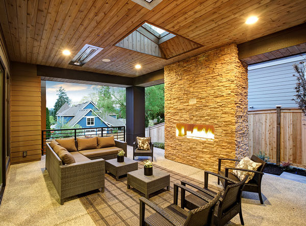 Covered patio connected to the home with heaters and a contemporary fireplace.