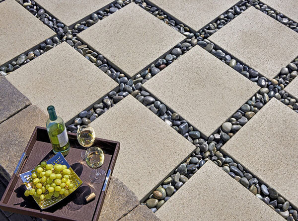 Polished loose pebbles in between square pavers.