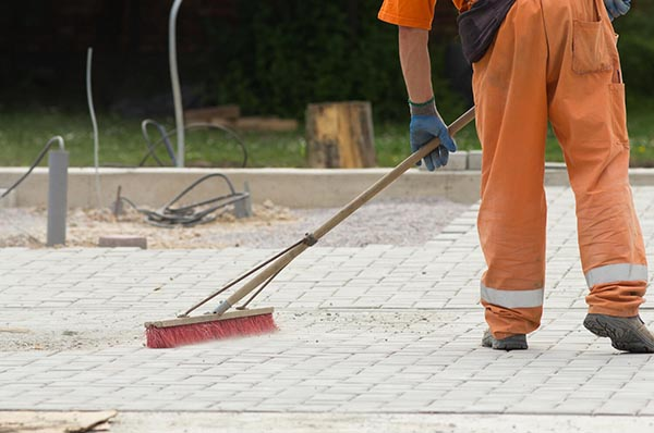 Worker cleaning pavers