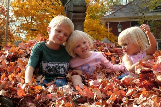 Children playing in fall leaves.