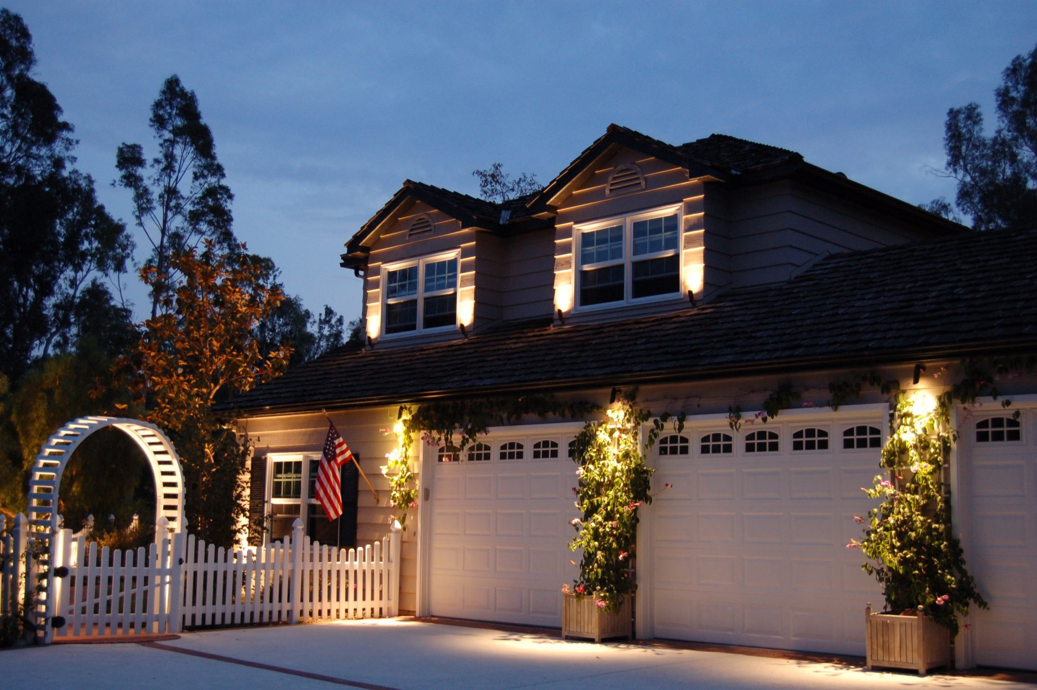 Front of house with outdoor lighting on home and walkway