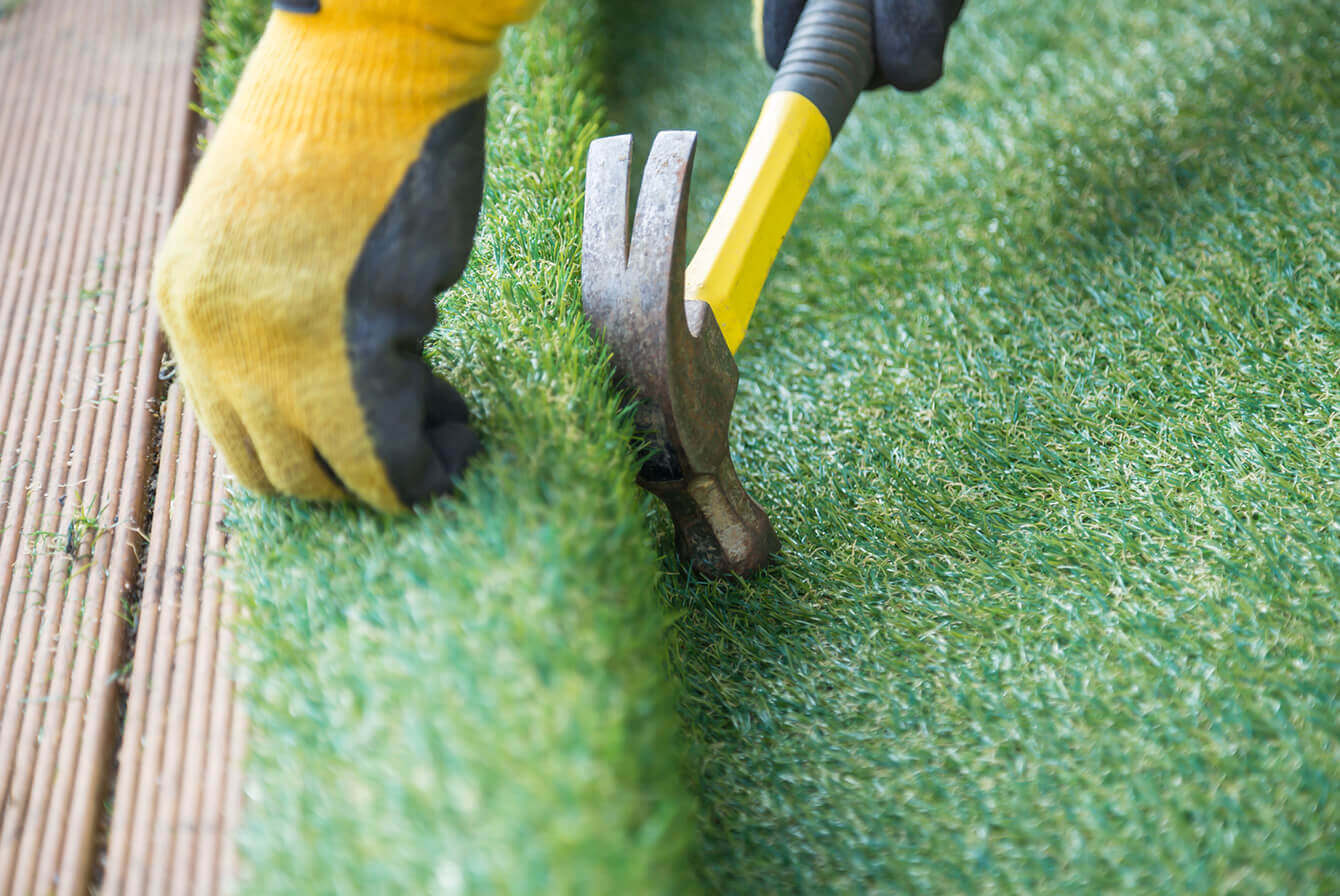 Worker repairing artificial turf seams.